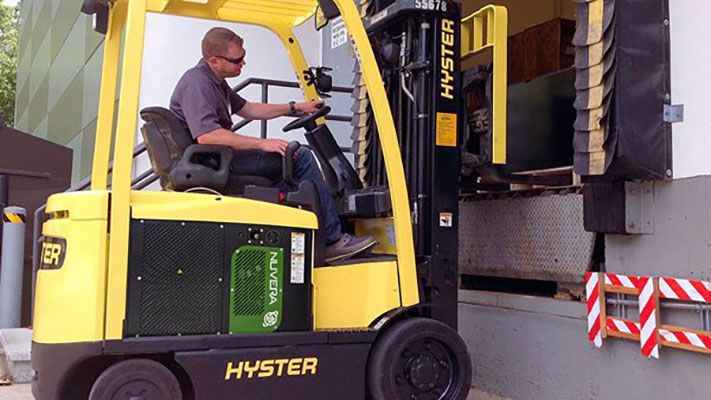 Man driving forklift, picking up cargo at a loading dock.