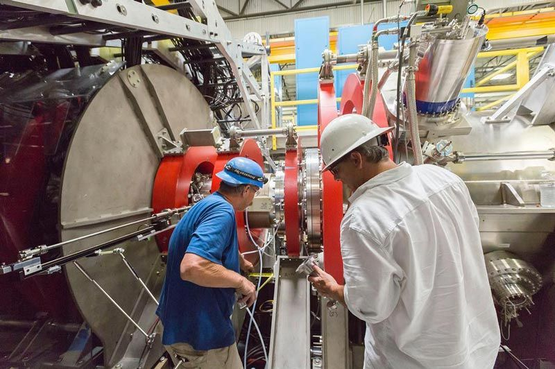 Two men, in hardhats, working on the fusion reactor.