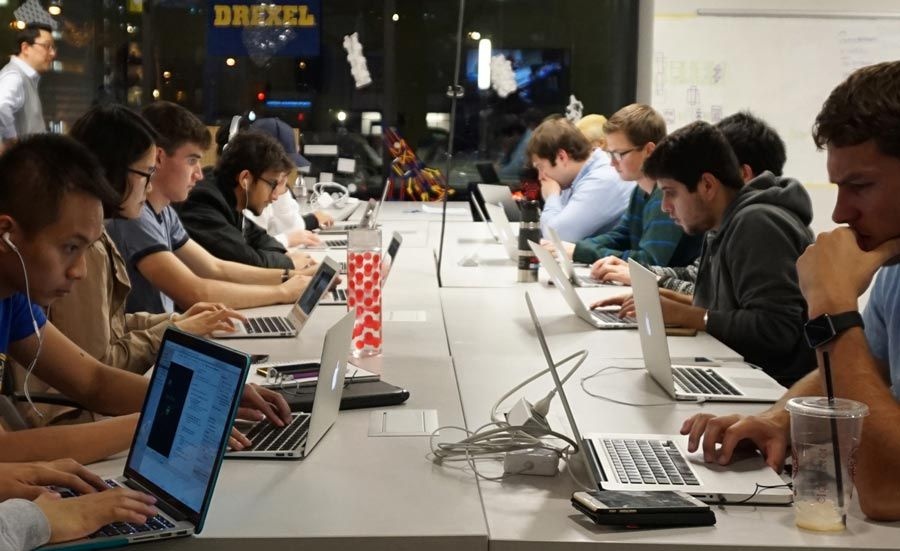 Students with laptops sitting along a long table in Drexel's ExCITe Center.